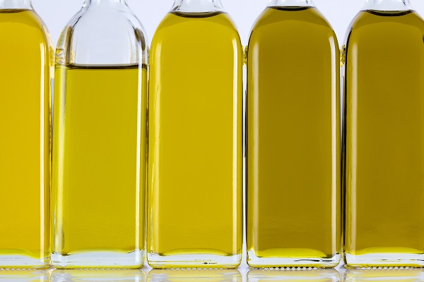 行とさまざまな色合いのオリーブオイルのボトル